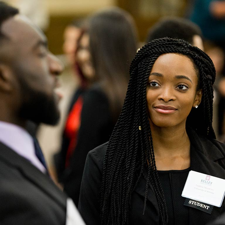 A student listens to another person speak at a career fair.