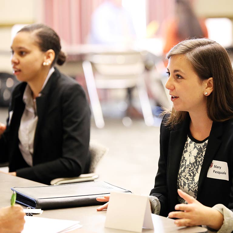 Two women speak at a career fair.
